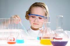 A little girl analyzing chemical liquid Stock Photos