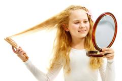 portrait of a little blond girl brushing hair before the mirror - stock photo