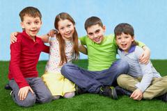 group of four children sitting on a green grass - stock photo