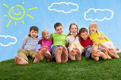 Group of happy children relaxing on the grass together Stock Photos