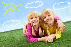 Portrait of cute twins lying on a green grass Stock Photos