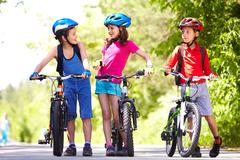 portrait of three little children with their bikes - stock photo