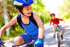 Two little boys riding bikes one after another Stock Photos
