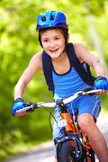 portrait of a little boy riding a bike - stock photo