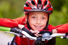 close-up of a little boy's face on bike looking at camera and smiling - stock photo