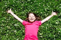 portrait of a joyful little girl lying on grass - stock photo