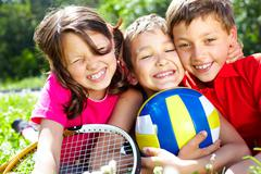 Three children with sports equipment embracing, looking at camera and smiling Stock Photos