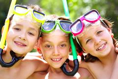 Three children with snorkels looking at camera and smiling Stock Photos