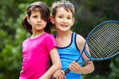 Portrait of a little girl and boy with badminton racket Stock Photos