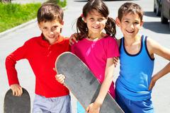 Portrait of three embracing children with skateboards looking at camera and smil Stock Photos