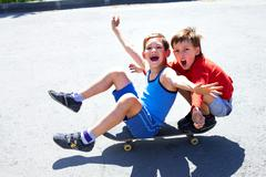two cheerful boys sitting on skateboard - stock photo