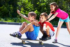 a girl pushing skateboard with two boys sitting on it - stock photo