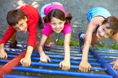 three little children climbing ladder and looking at camera - stock photo