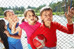 Three children at playground standing behind the netting Stock Photos