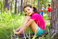 portrait of a young girl sitting on ground in wood - stock photo