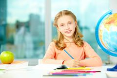 portrait of cute schoolgirl with blue pencil looking at camera in classroom - stock photo