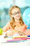 portrait of cute schoolgirl looking at globe through eyeglasses - stock photo