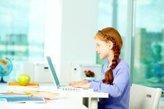 Portrait of smart schoolgirl sitting in classroom and typing Stock Photos