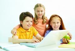 Portrait of smart schoolgirls and schoolboy looking at the laptop in classroom Stock Photos