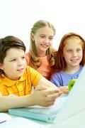 portrait of smart schoolgirls and schoolboy looking at the laptop in classroom - stock photo