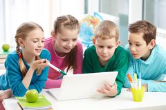 Portrait of smart schoolgirls and schoolboys looking at the laptop in classroom Stock Photos
