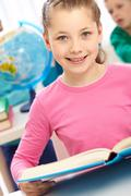 Portrait of smart schoolgirl with open book looking at camera Stock Photos