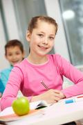 portrait of smart schoolgirl making notes and looking at camera - stock photo