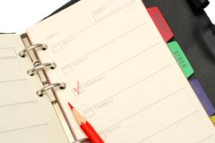 Open organizer and red pencil Stock Photos