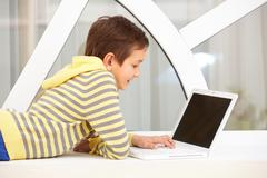portrait of smart schoolboy typing on laptop - stock photo
