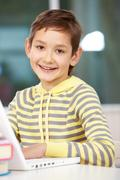 portrait of smart schoolboy looking at camera while typing on laptop - stock photo