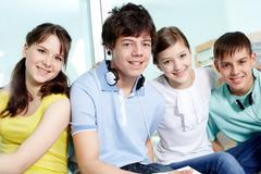 Portrait of four smiling teenagers looking at camera Stock Photos