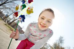 portrait of cute girl with toy looking at camera outdoors - stock photo