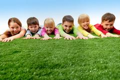 group of happy children lying on a grass and stretching their arms - stock photo