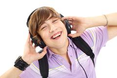 portrait of happy teenage boy with headphones and backpack - stock photo