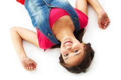 cute girl lying and smiling at camera in isolation - stock photo