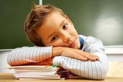 Portrait of cute lad keeping his head on copybooks in classroom Stock Photos