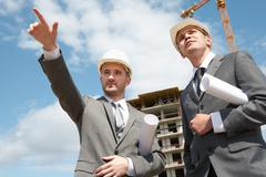Photo of young engineer showing something to his colleague during meeting at bui Stock Photos