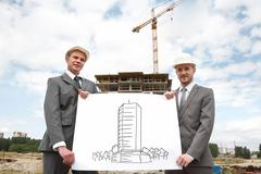 Portrait of two successful builders holding large sheet of paper with sceme of c Stock Photos