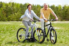 portrait of happy mature couple on bicycles - stock photo