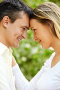 portrait of young couple looking at each other outdoors - stock photo