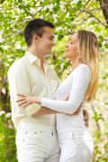 portrait of young amorous couple looking at each other in park - stock photo