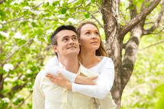 Portrait of happy couple looking upwards in park Stock Photos