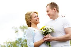 Laughing couple embracing and looking at each other outdoors Stock Photos