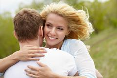 portrait of happy girl hugging handsome man outside - stock photo