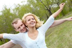 portrait of happy couple stretching arms in natural environment - stock photo