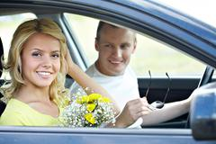 happy woman with bunch of flowers looking at camera in the car - stock photo
