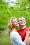 Portrait of young couple embracing and looking upwards outdoors Stock Photos
