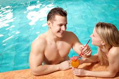 photo of happy couple in swimming pool chatting with one another - stock photo
