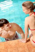 Photo of happy couple in swimming pool chatting with one another Stock Photos