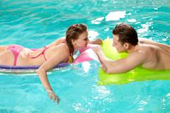 Handsome guy and pretty girl looking at one another in swimming pool Stock Photos